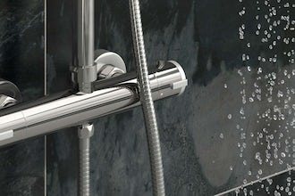 What is a thermostatic shower valve and how does it work?