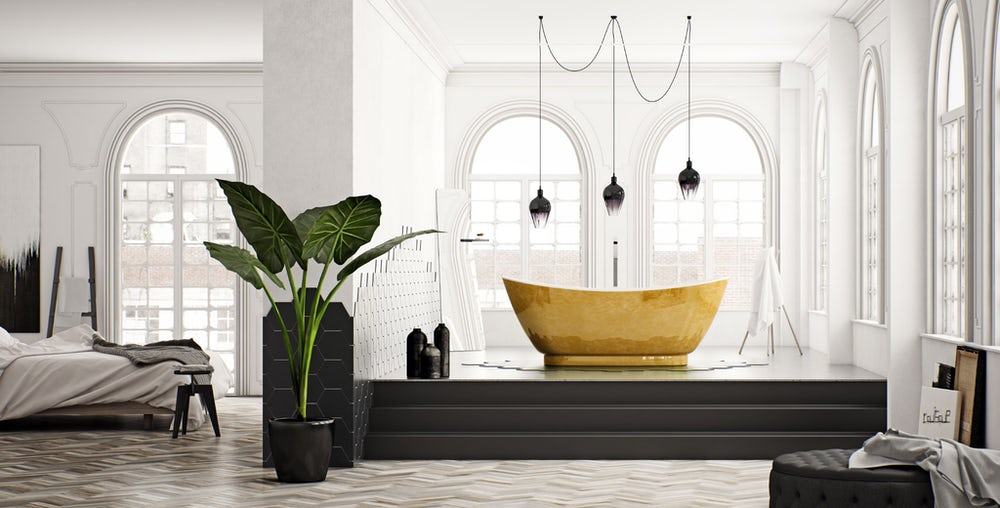 Opulent gold leaf coated Galvez freestanding bath on a raised floor with a modern light fitting above