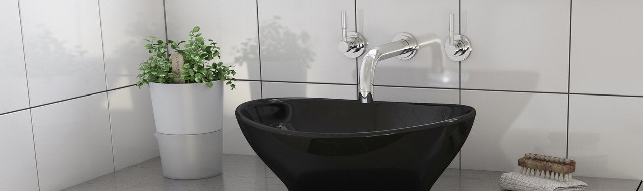 A Contemporary Black Round Basin With A Chrome Wall Mounted Tap
