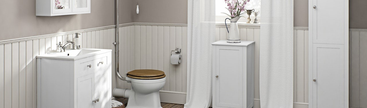 A traditional bathroom set-up with a white vanity unit and tall whit cupboards