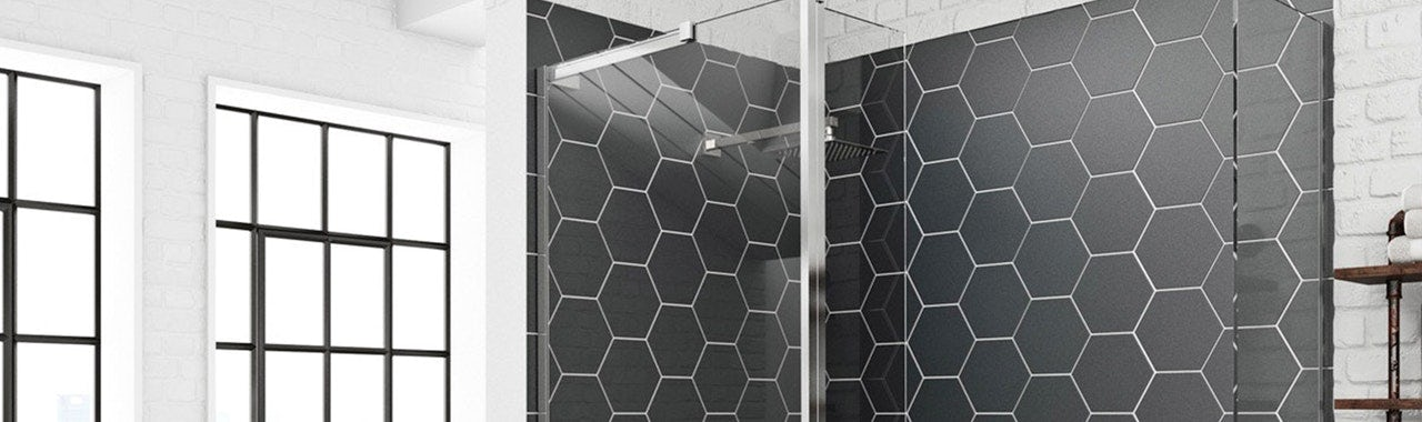 A shower enclosure with black hexagonal tiles
