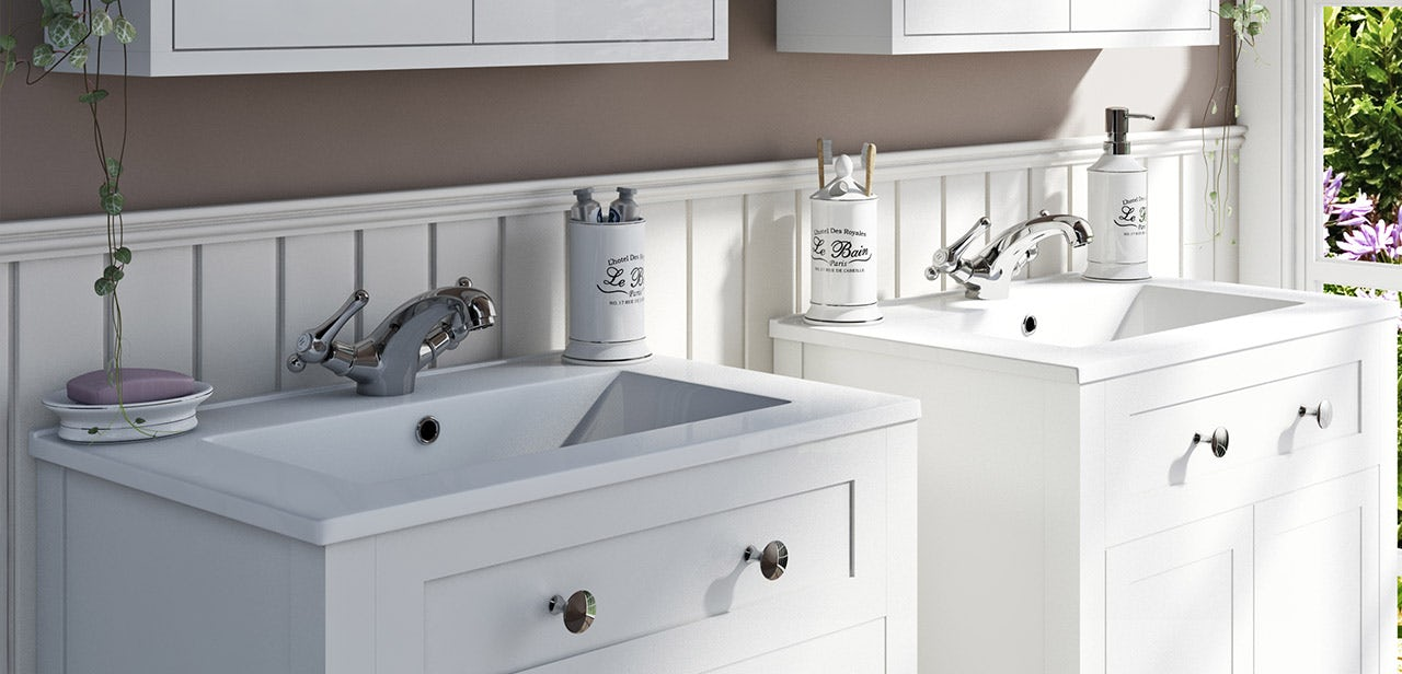 A range of traditional bathroom accessories on a shelf including a toothbrush holder, soap dispenser and a cup