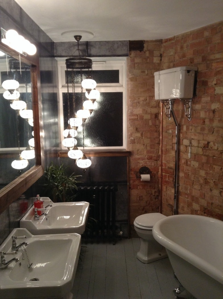 Rough brick walls and exposed metal are gaining popularity in bathrooms