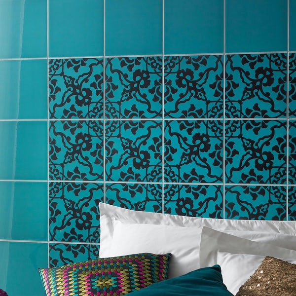 bed pillows in front of a tiled turquoise wall with black pattern