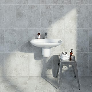 two bathroom basins with accessories on a grey tiled wall